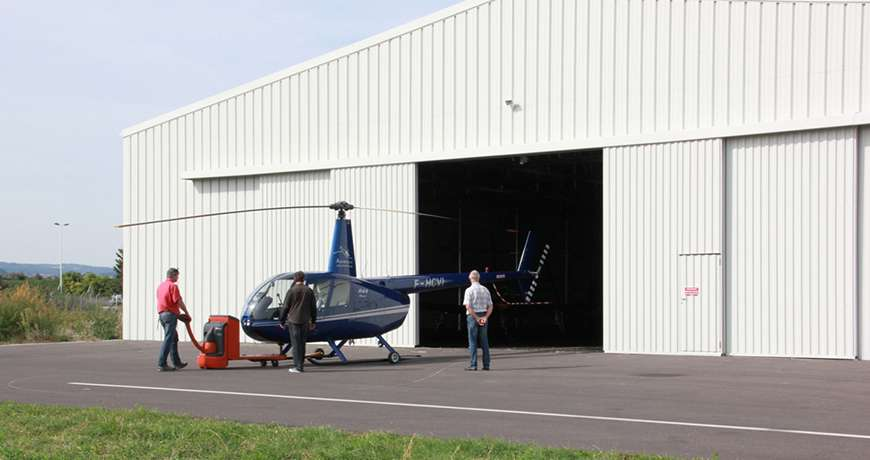 White aircraft and helicopter hangar with a blue heli parked infront of the steel building.